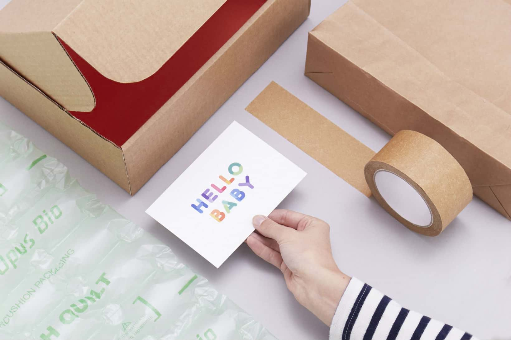 The packaging we use at KIDLY: cardboard box, 'Hello Baby' card, paper strapping tape, paper shipping bags and air-filled box infill